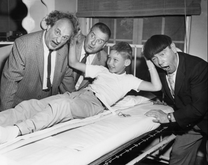 "June 22, 1959 – The Three Stooges, ""Larry"" Fine left, Joe DeRita ""Curley Joe,"" center, and ""Moe"" Howard, far right, ham it up at the Children's Hospital with 10-year-old patient Fred Reinholdt. (Edward Nolan/Baltimore Sun)"